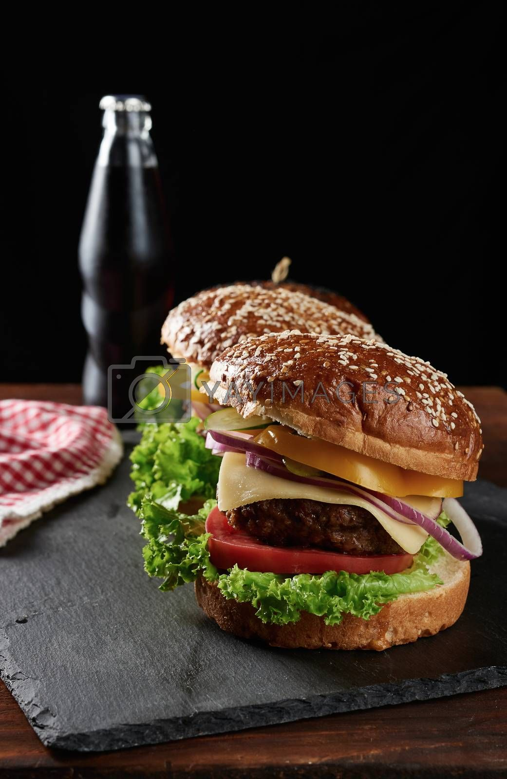 delicious burgers with fried beef cutlet and onions, tomato and crispy white wheat flour bun with sesame seeds. Fast food on a wooden board, behind a bottle with a drink