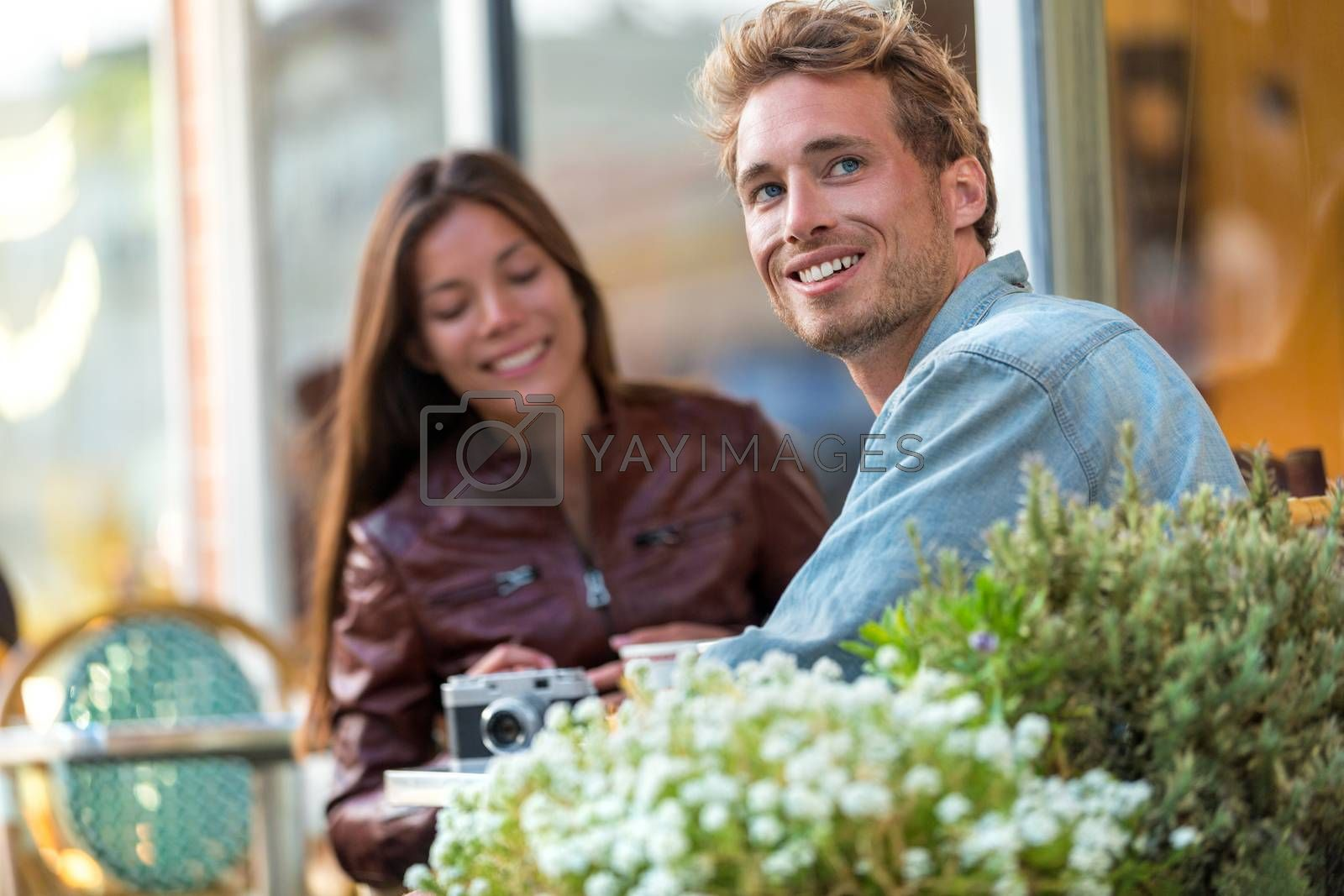 Young urban man enjoying sitting at restaurant table with friend in city. European travel couple vacation. Casual people lifestyle.