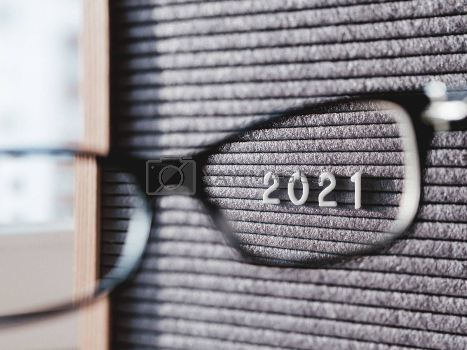 Letterboard with numbers 2021 through eyeglasses. Flat lay concept of 2021 year results. 2021 review. Social, political or economical issue. Closer look on problems and achievements.
