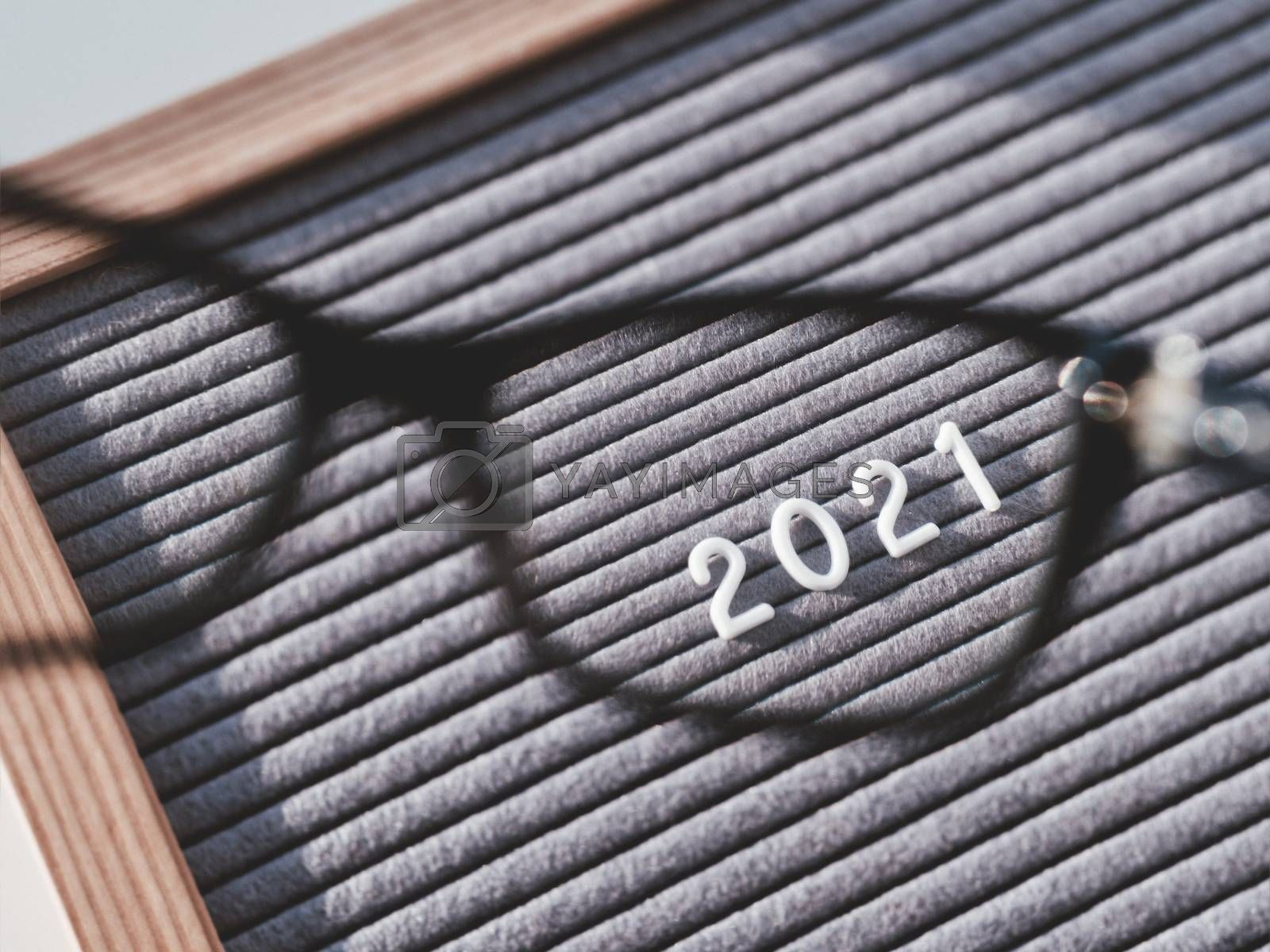 Top view on letterboard with numbers 2021 through eyeglasses. Flat lay concept of 2021 year results. 2021 review. Social, political or economical issue. Closer look on problems and achievements.