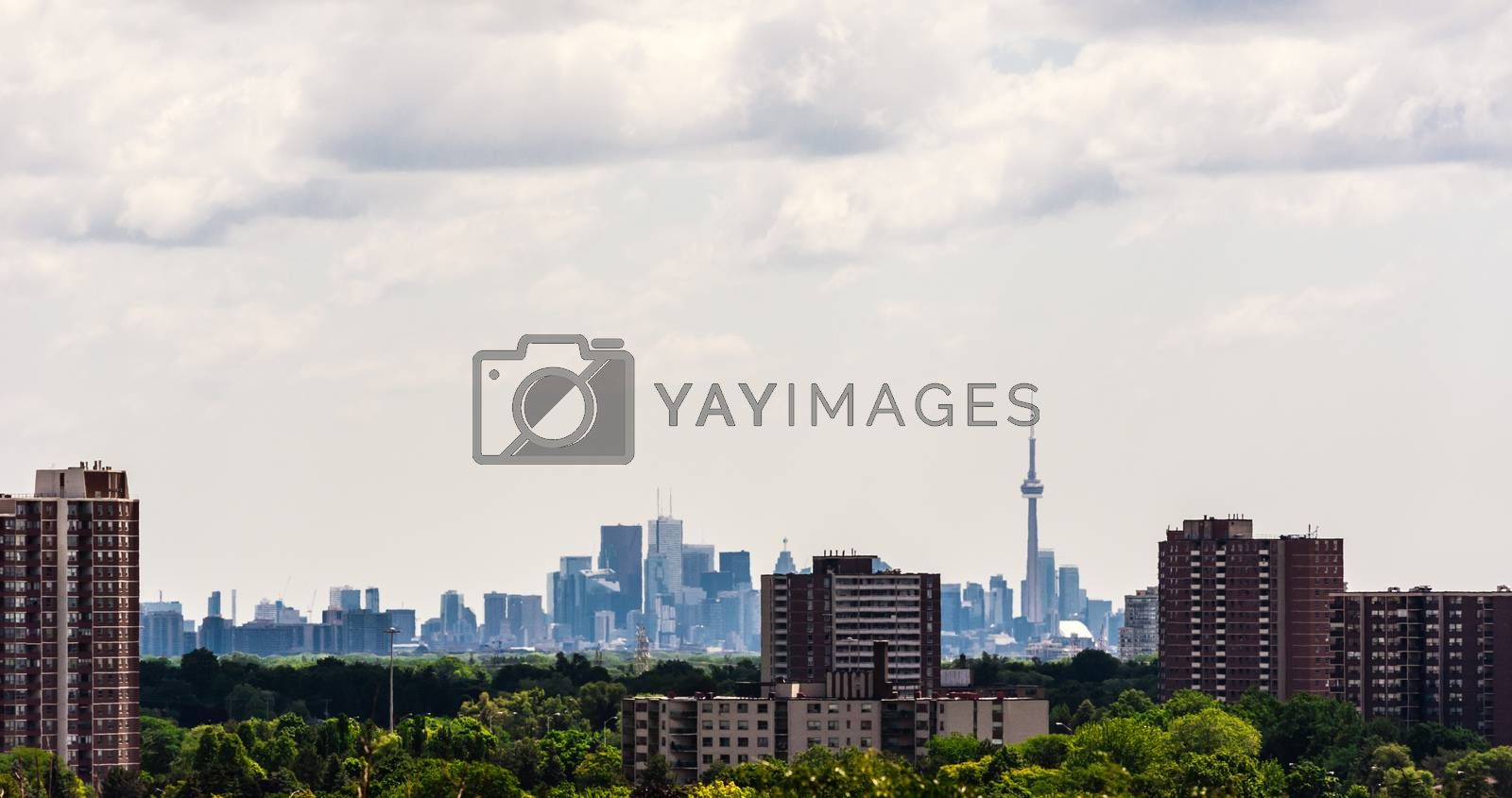 TORONTO, CANADA - JULY 10, 2016: Older apartment buildings stand among trees in suburban Etobicoke, with dense downtown Toronto in the distance.