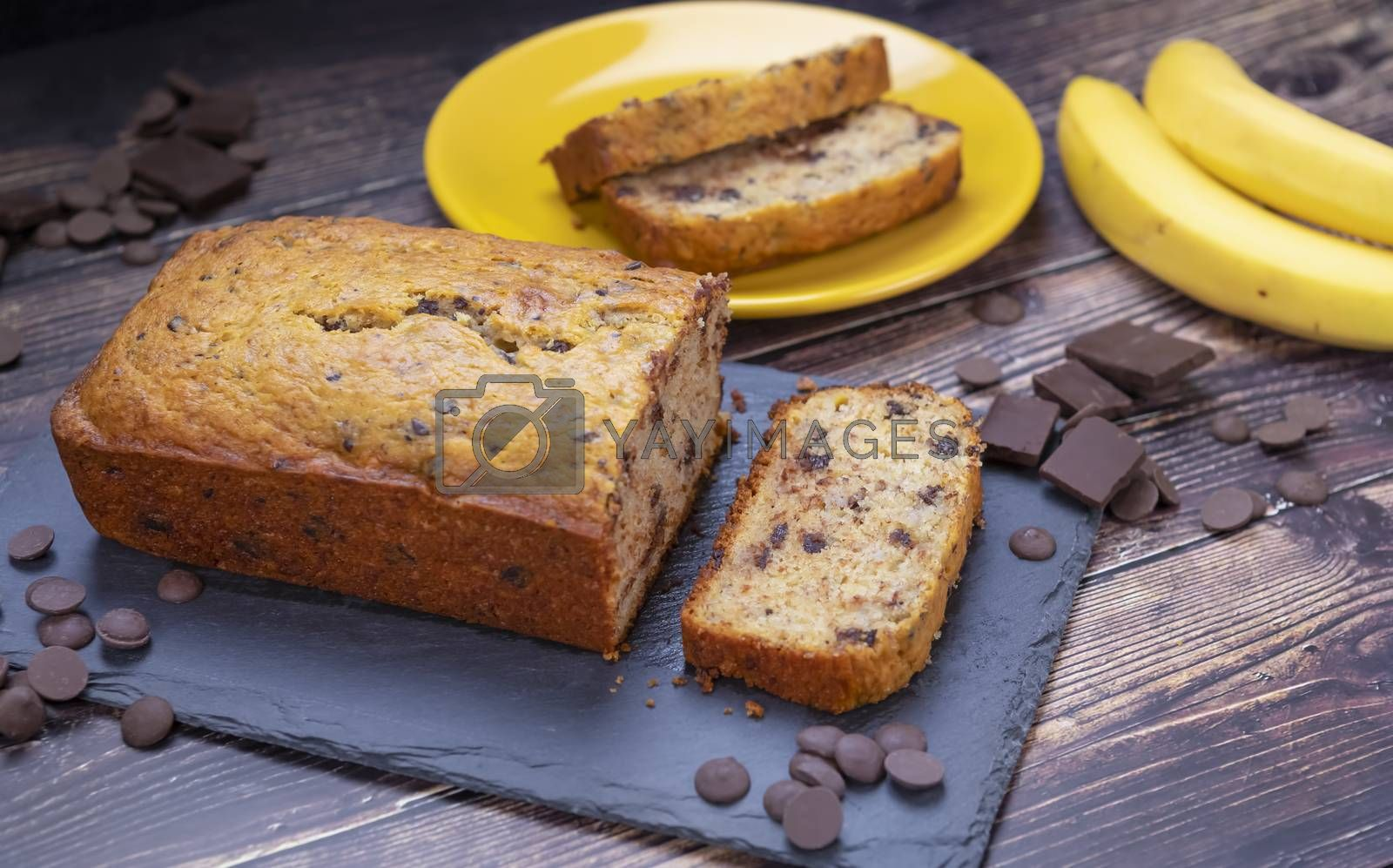 Banana bread on cutting board with chocolate chips and fresh banana in background.