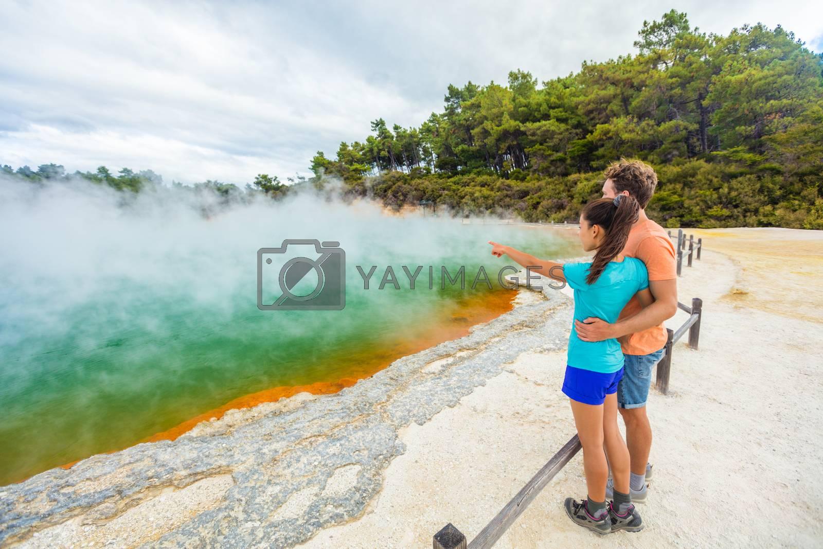 New Zealand travel tourists couple at Champagne pool at Wai-O-Tapu pools Sacred Waters. Tourist attraction in Waiotapu, Rotorua, north island. Active geothermal area, Okataina Volcanic Centre, Taupo.