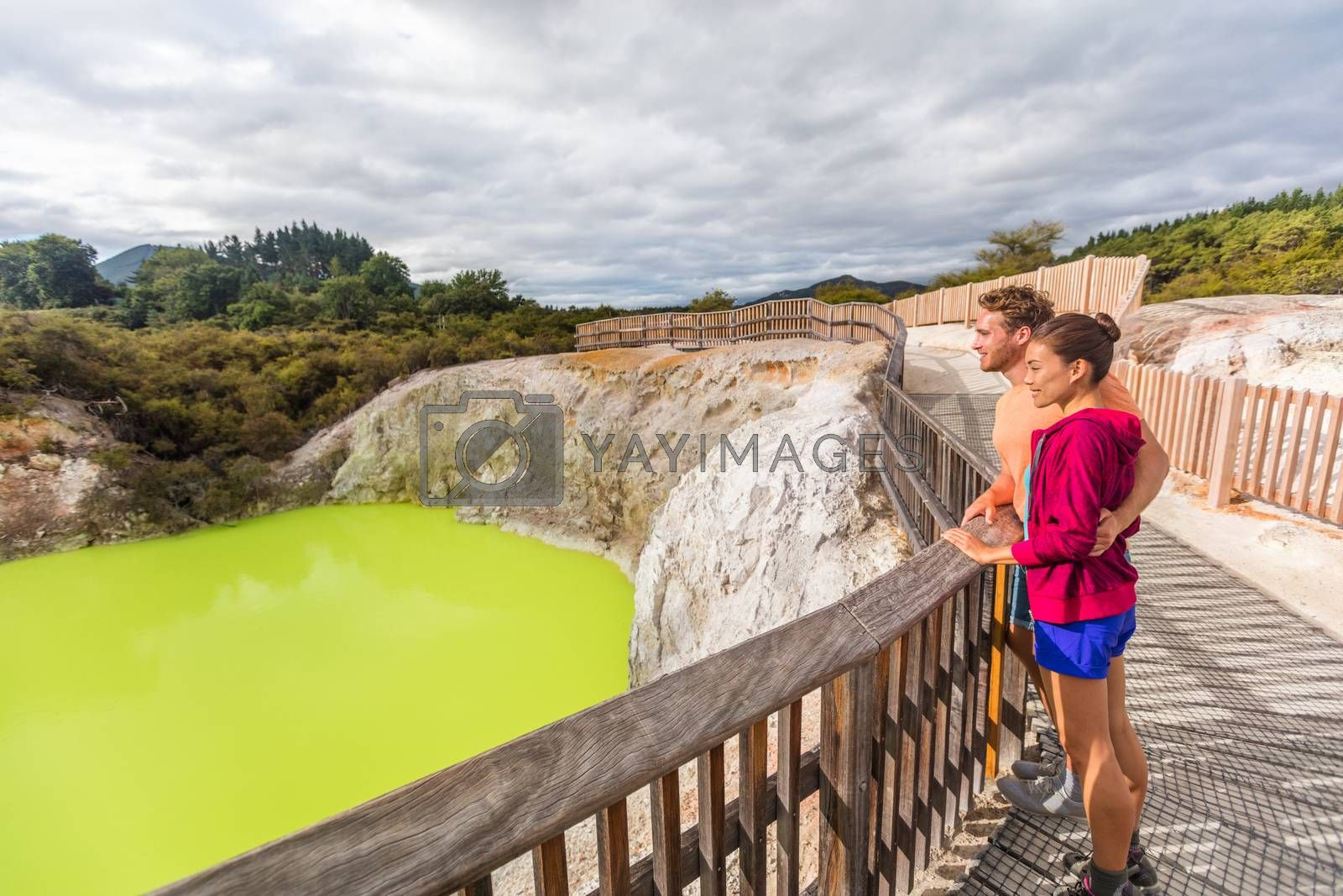 New Zealand travel tourists looking at green pond. Tourist couple enjoying famous attraction on North Island, geothermal pools at Waiotapu, Rotorua.