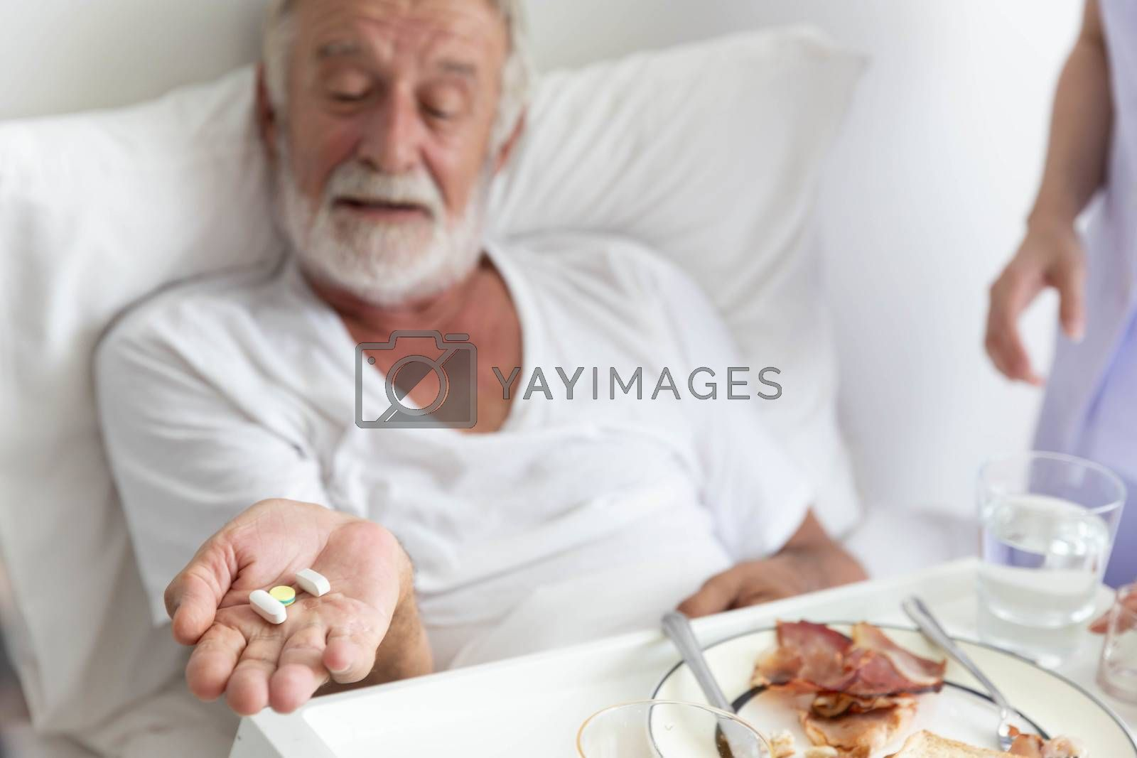 Nurse give medicine pills to elderly senior patient while he is in his bed with breakfast