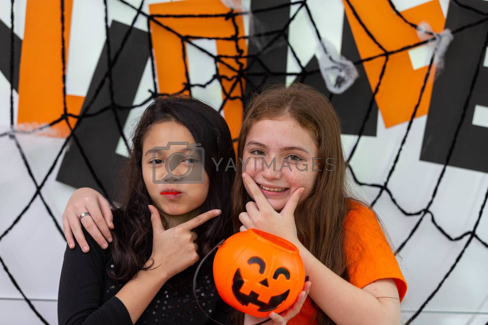 Happy Halloween by two sisters in carnival costume in decorated house