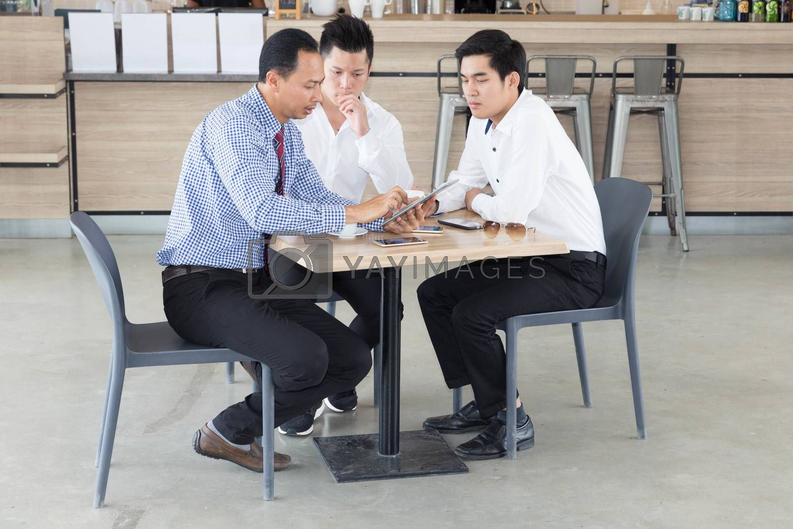 Three Asian businessmen discussing while having coffee together