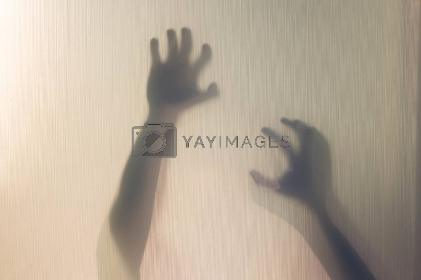 Silhouette of arms and hands behind curtain with soft focus and blur