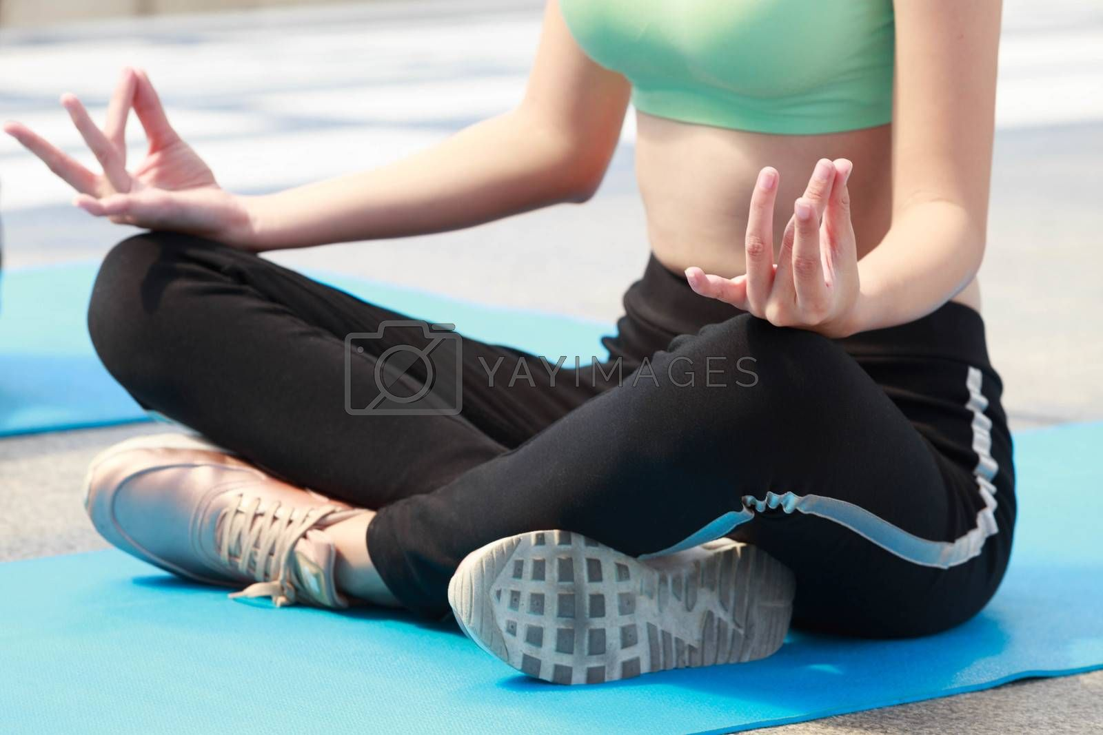 Woman in sportwear practicing yoga pose outdoor, under light with shadow