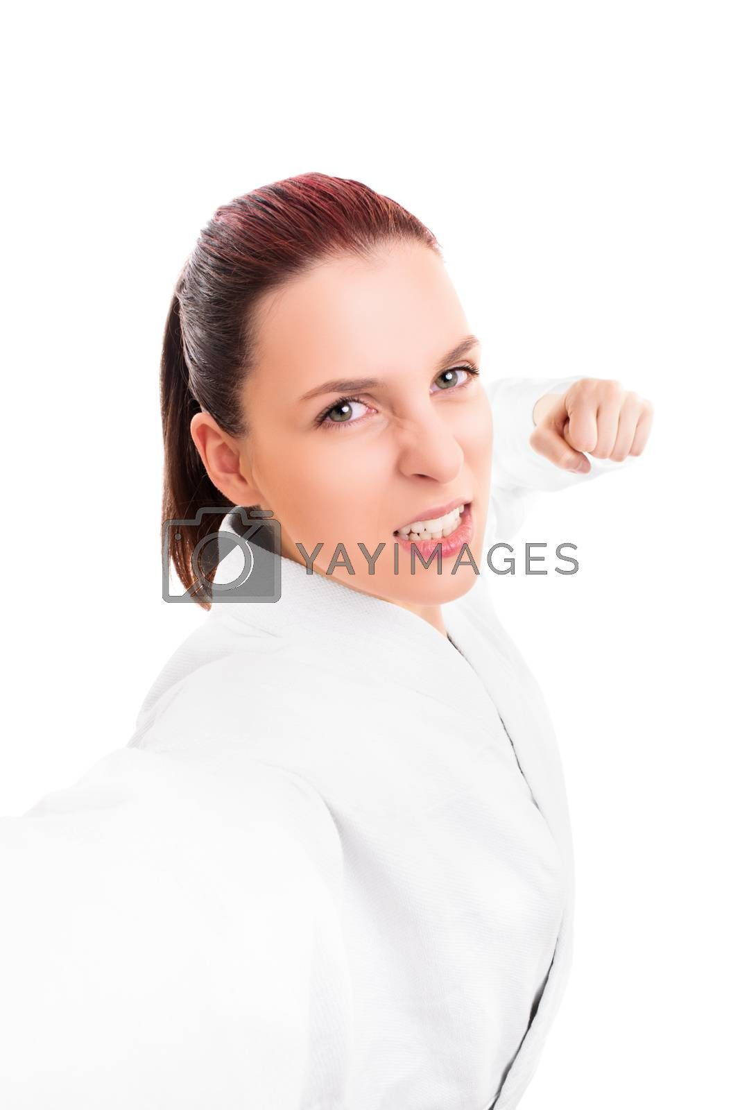 Close up portrait of a beautiful young girl in white kimono with the fists up punching the camera, isolated on white background. Martial art concept.