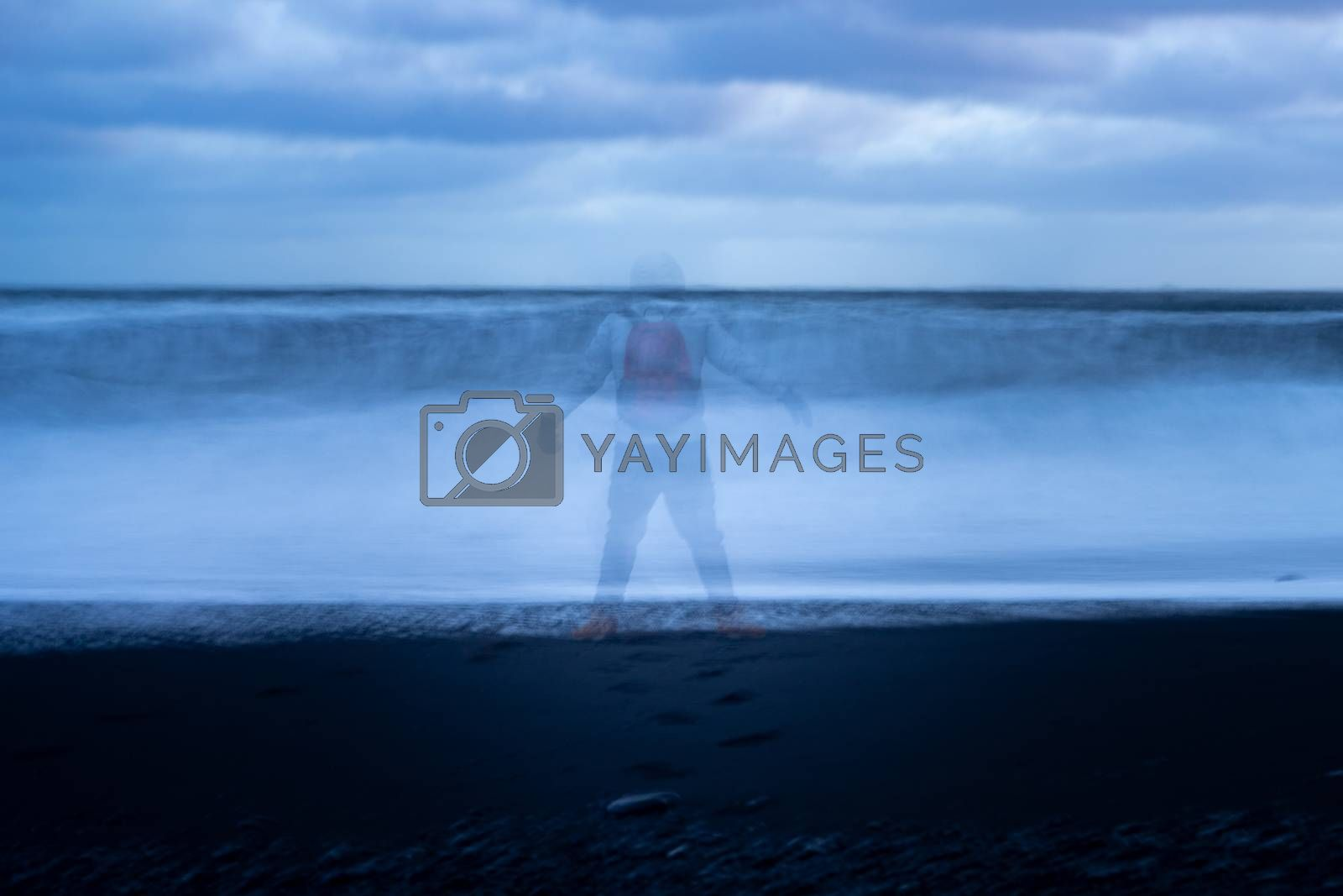 Male shadow stands against the waves on the black beach in Iceland longtime explosure