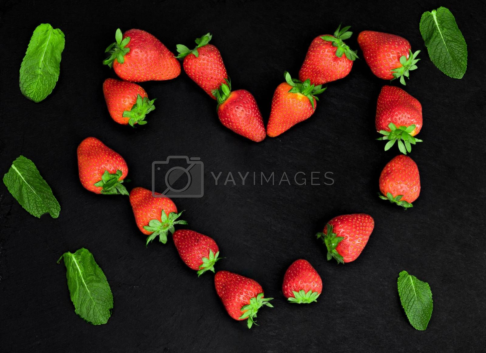 Fresh red strawberries shaped into a heart arranged on a slate as a symbol of love