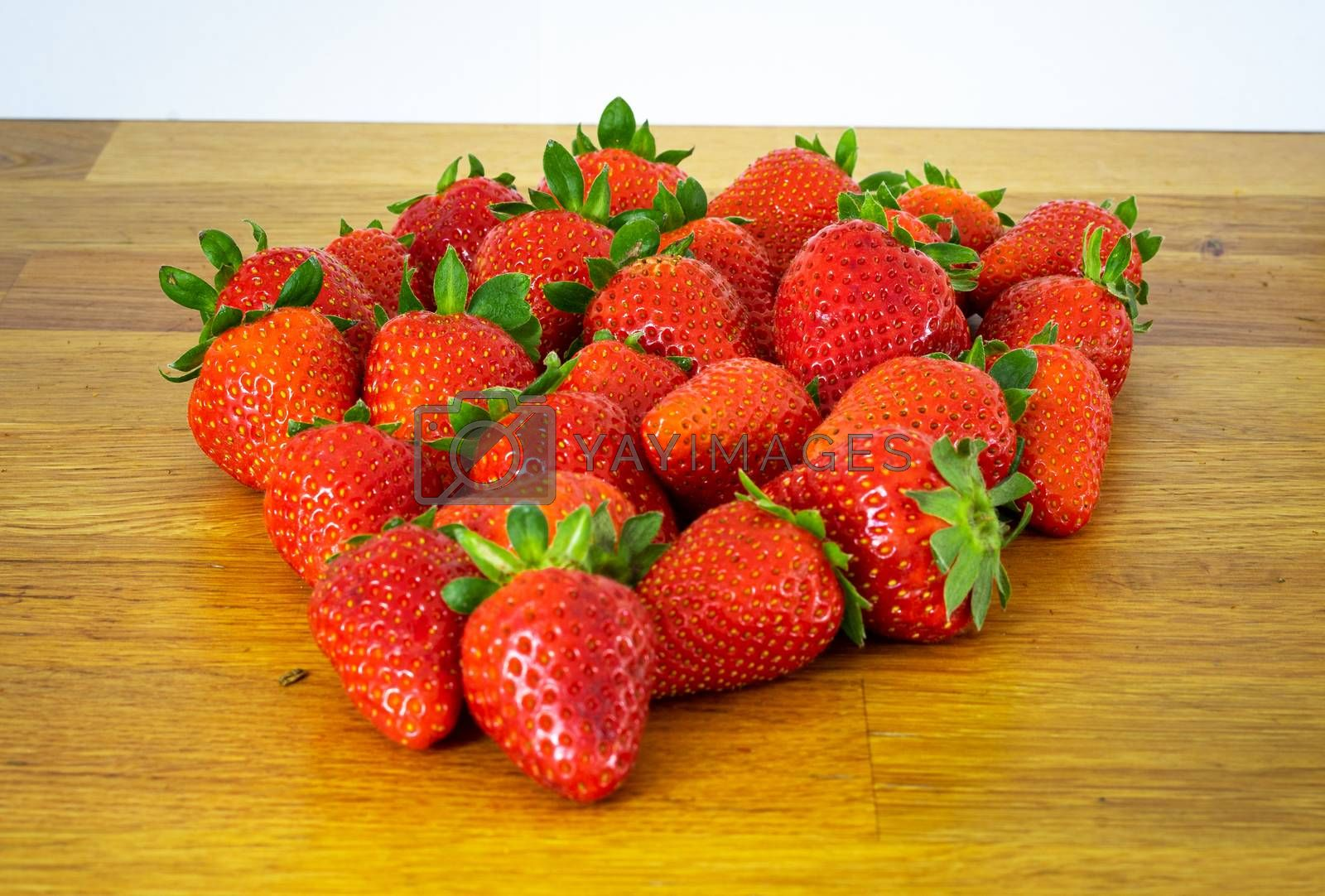 Fresh red strawberries shaped into a heart on a woody background in the kitchen