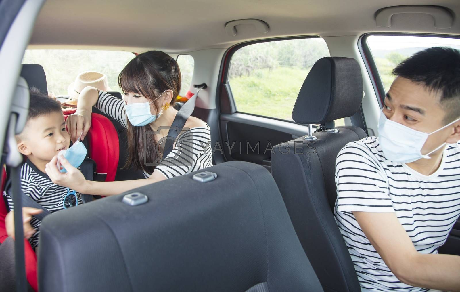 family with children rides in  car and mother help child wear medical mask