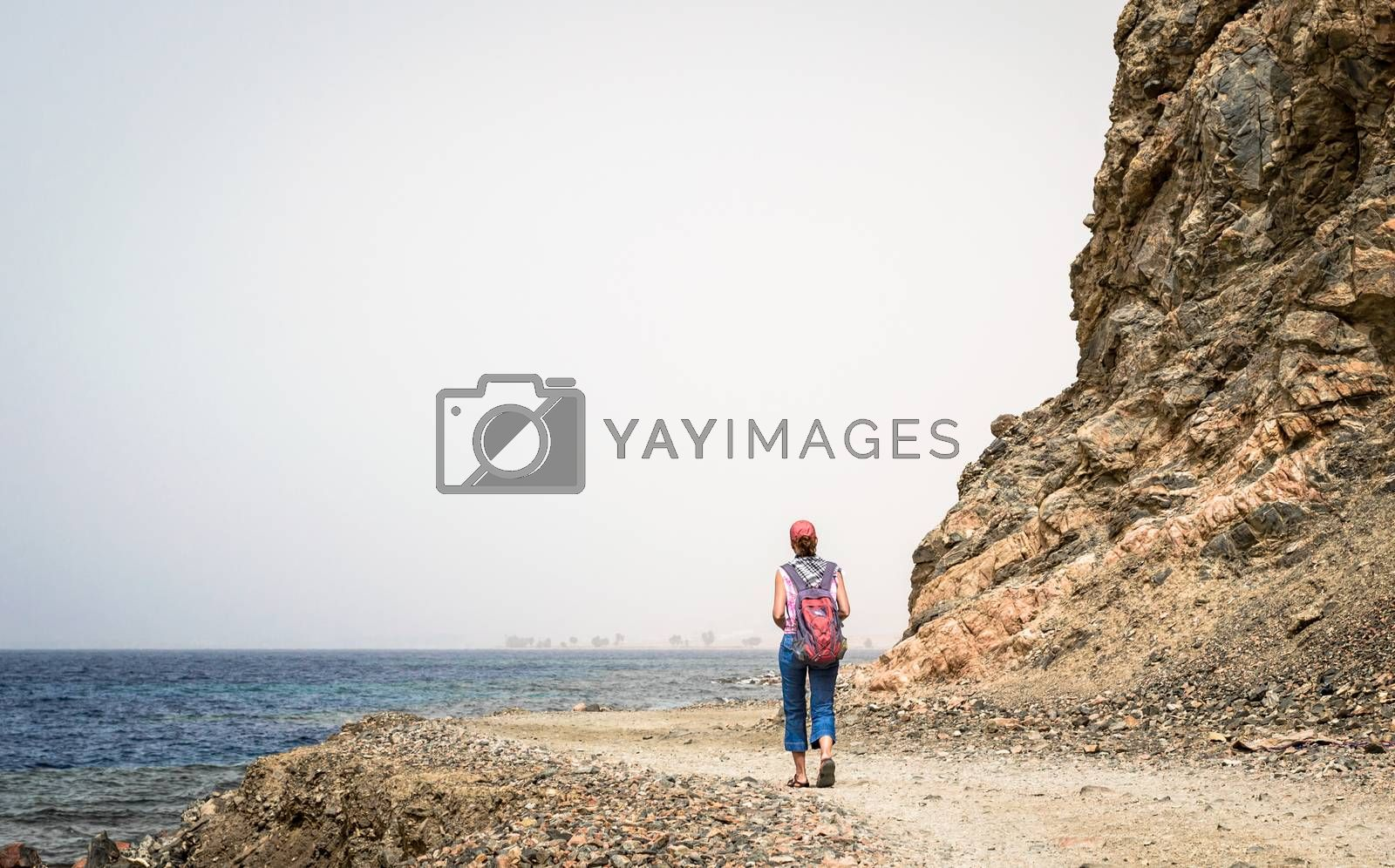 young girl tourist in a red cap with a backpack goes along the rocky shore of the Red Sea