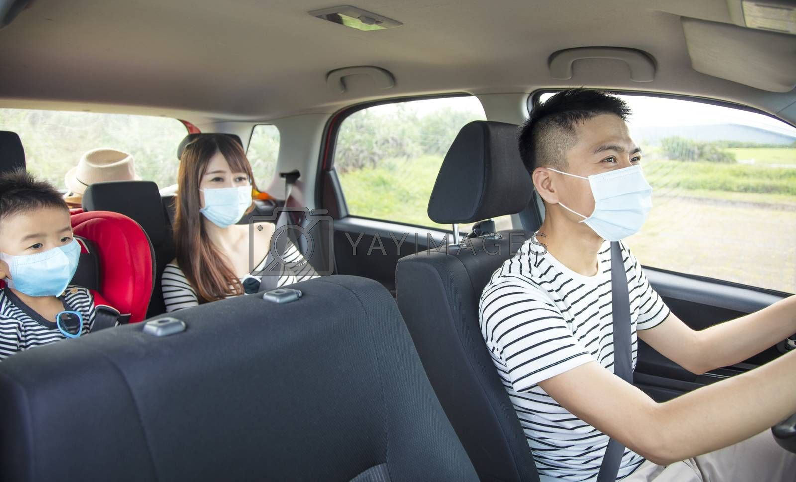 asian family with children rides in their car and wear medical masks