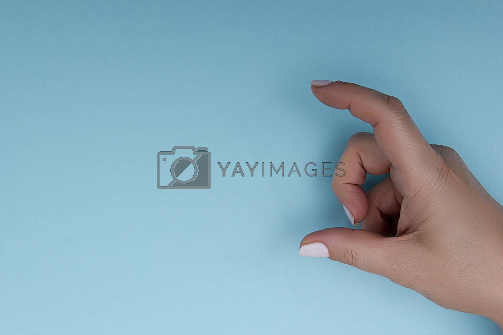 Female hand measuring or holding invisible item while showing small amount of something