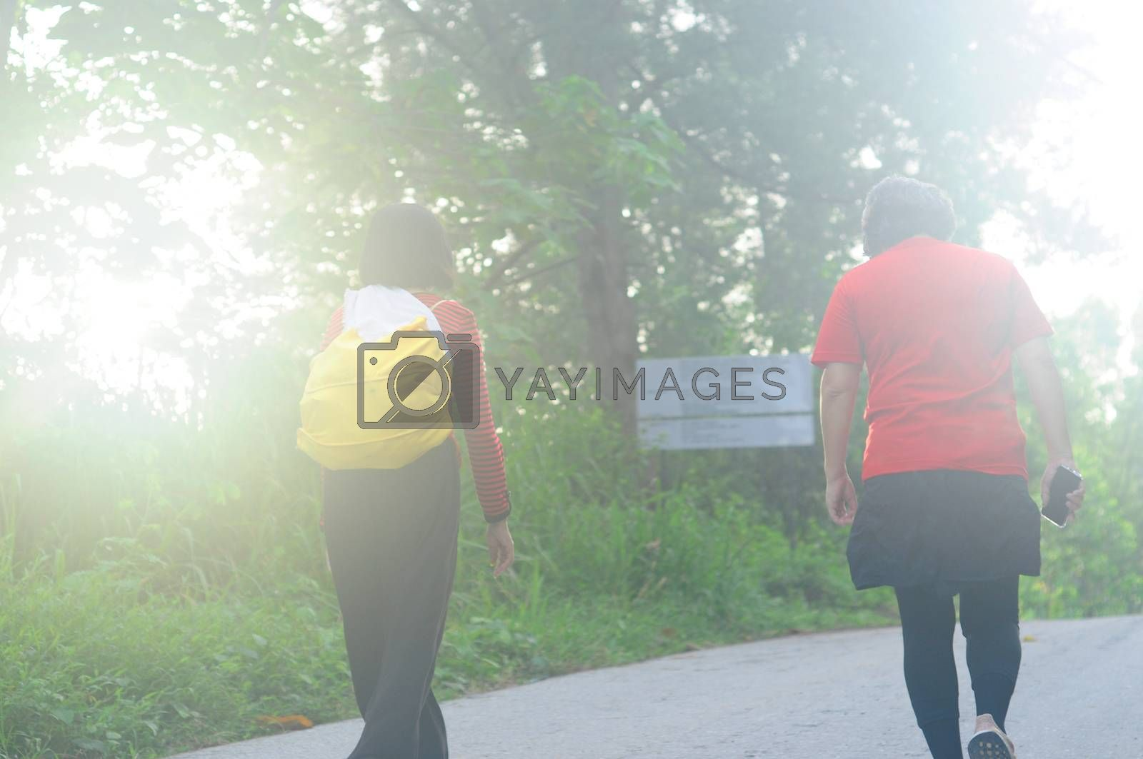 Vintage soft focus of an asian woman traveler with backpack walking in forest.Adventure, travel people concept.
