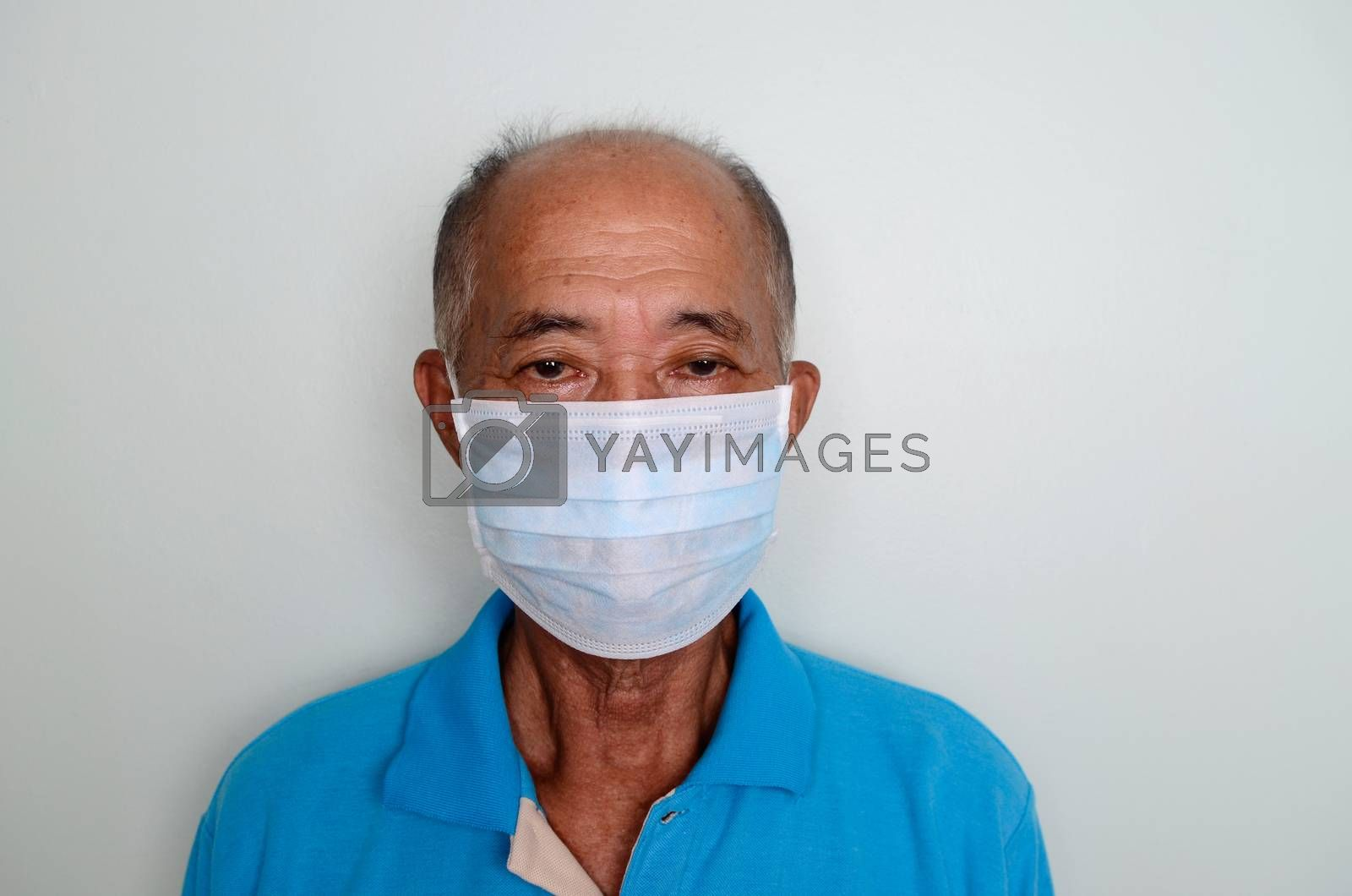 Portrait of an asian senior man, 60 years old wearing medical mask. A concept of the danger of coronavirus for the elderly.