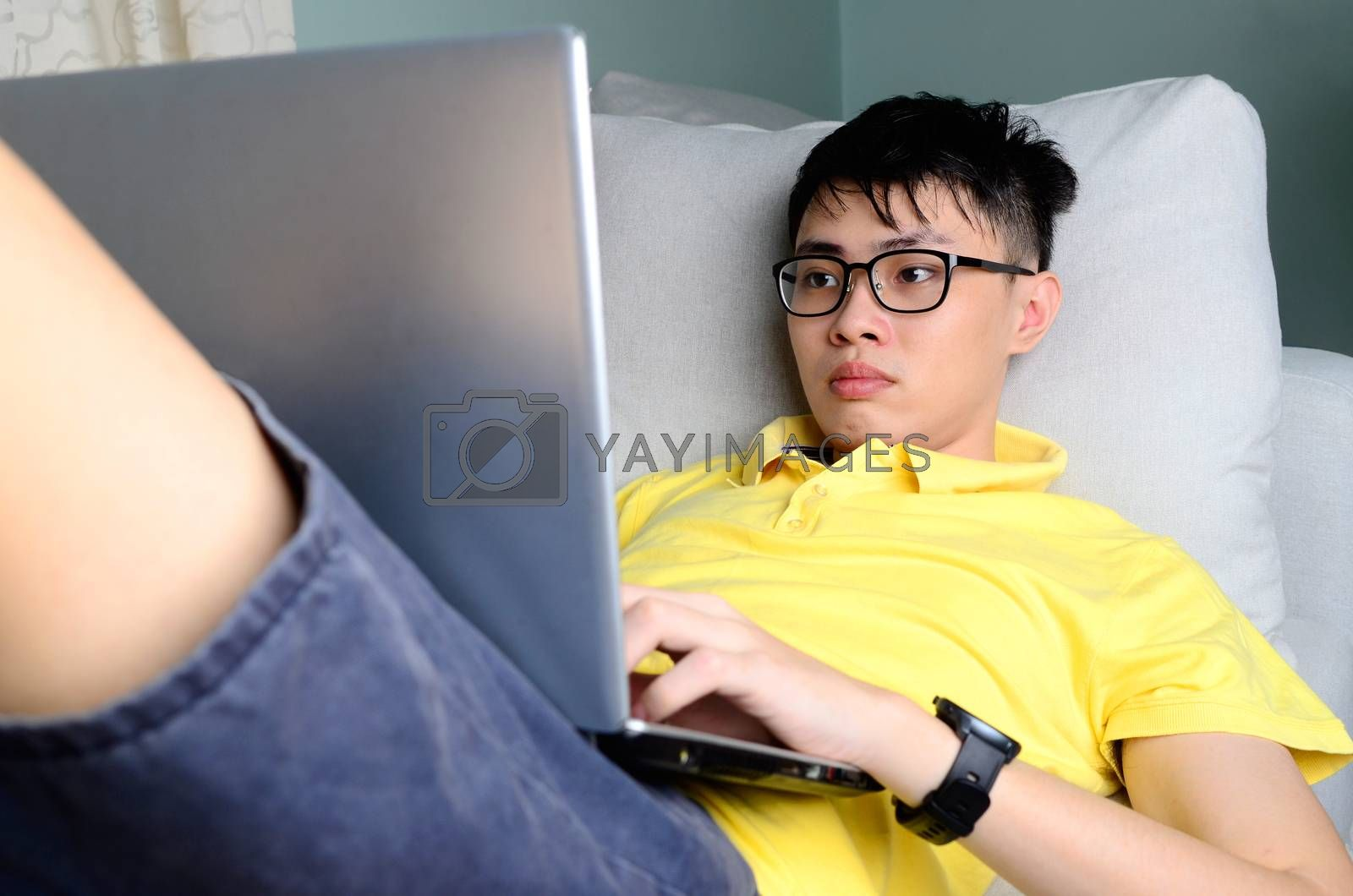 An asian young  man is working from home during Coronavirus or Covid-19 quarantine, coronavirus covid 19 infected patient in coronavirus covid 19 quarantine room using computer.