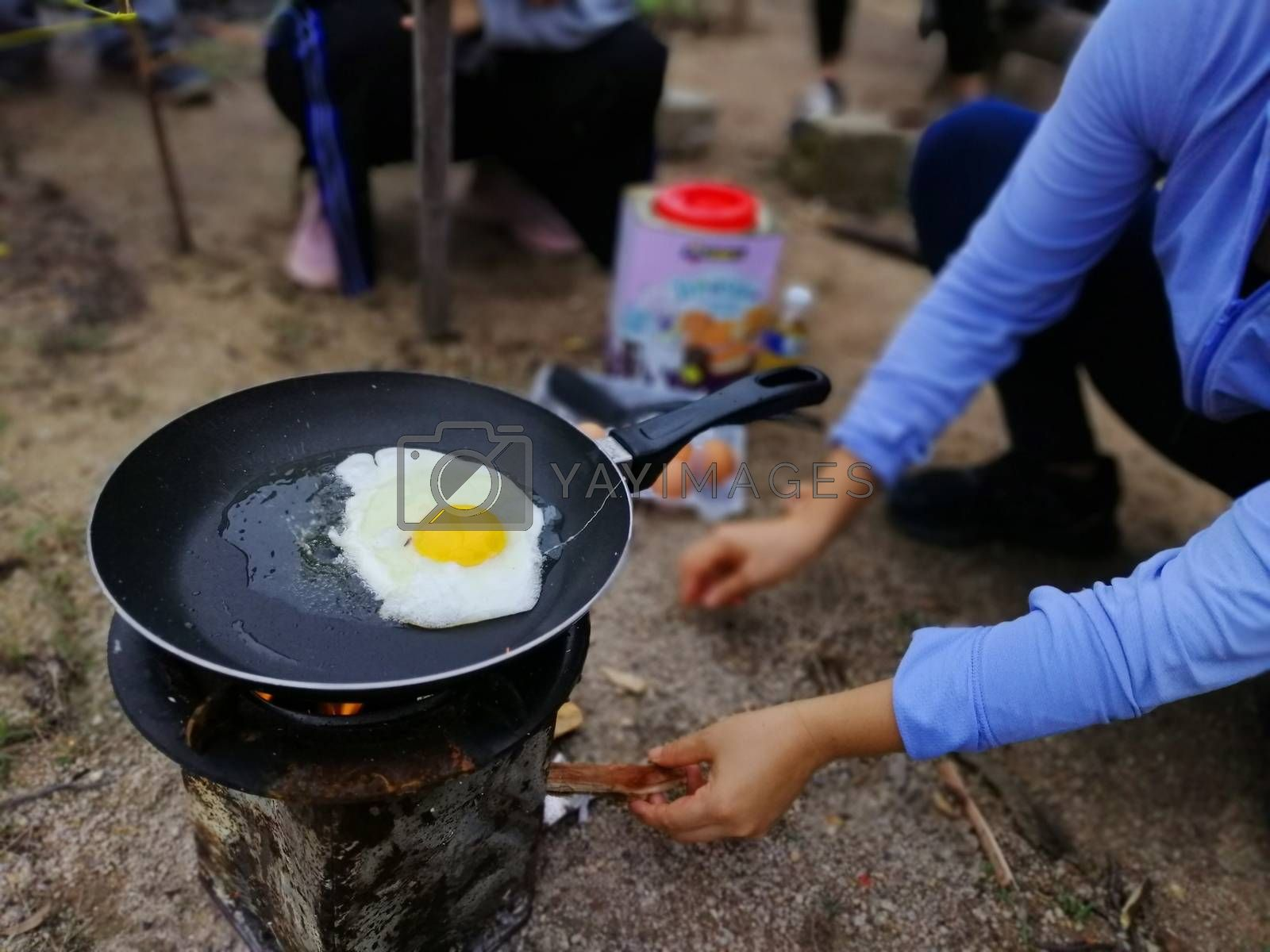 Cooking breakfast on campfire in cast iron pan with selective focus.
