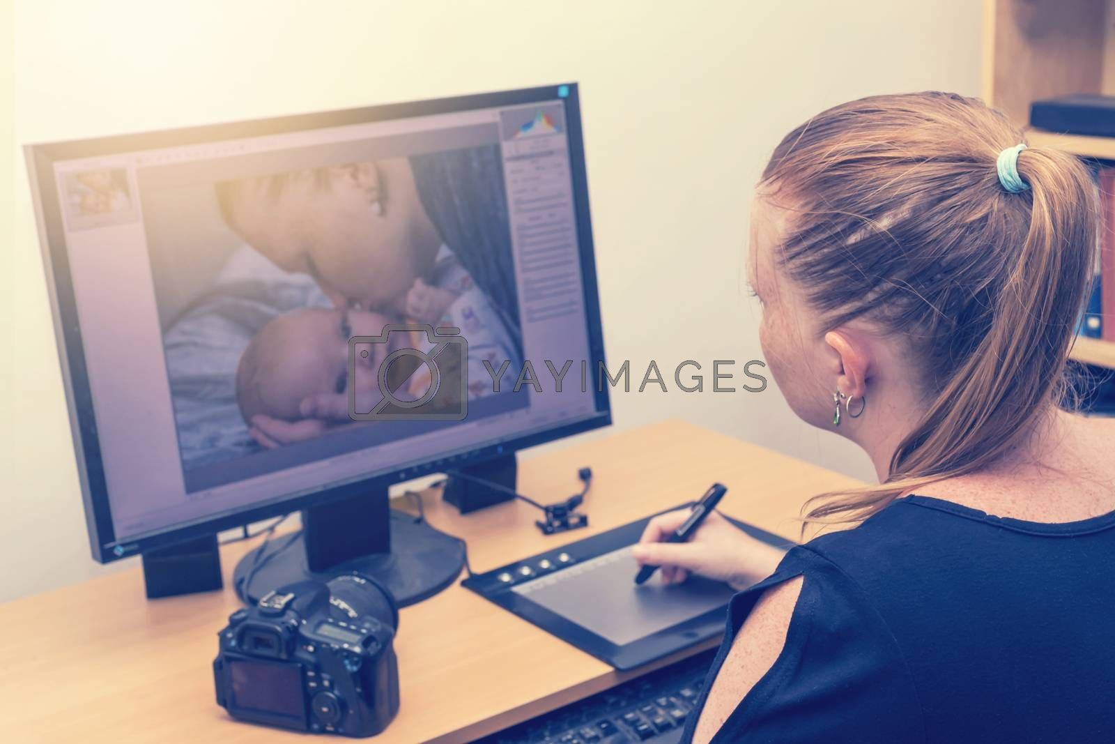 Young woman is editing photos by a graphics tablet and graphics software. Photo of kissing mother of her baby is on computer monitor in front of her. All potential trademarks are removed.