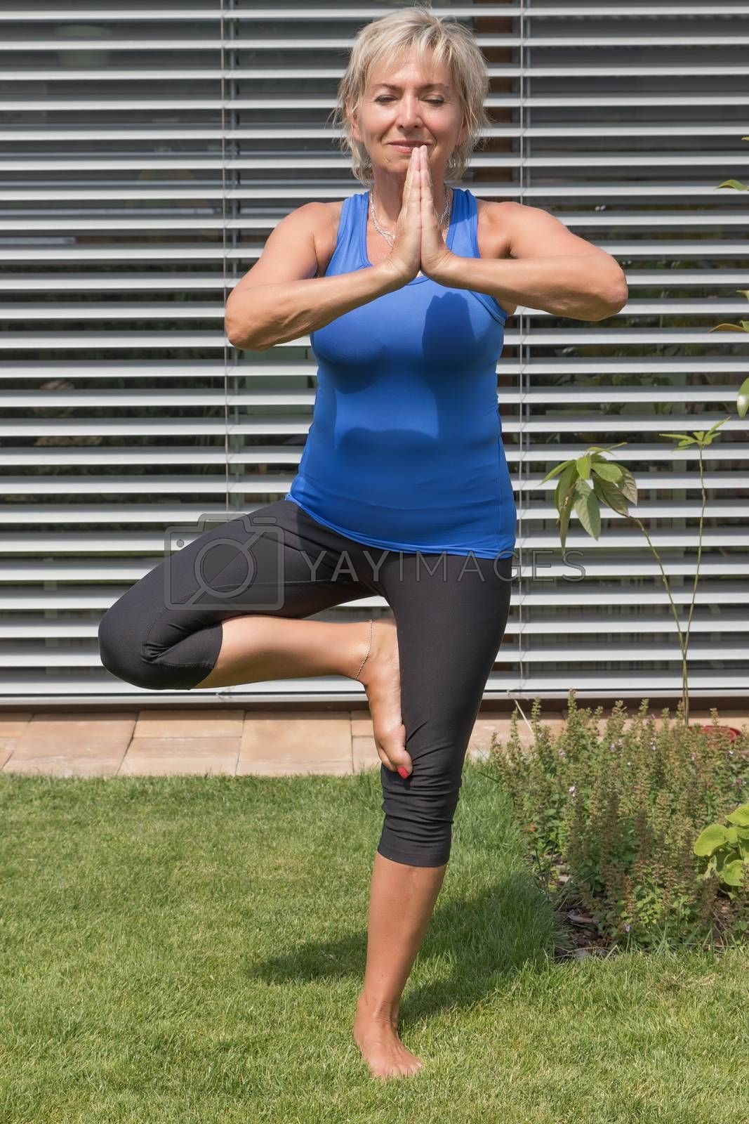 Senior blond woman is practicing yoga standing in tree pose asana in the garden.
