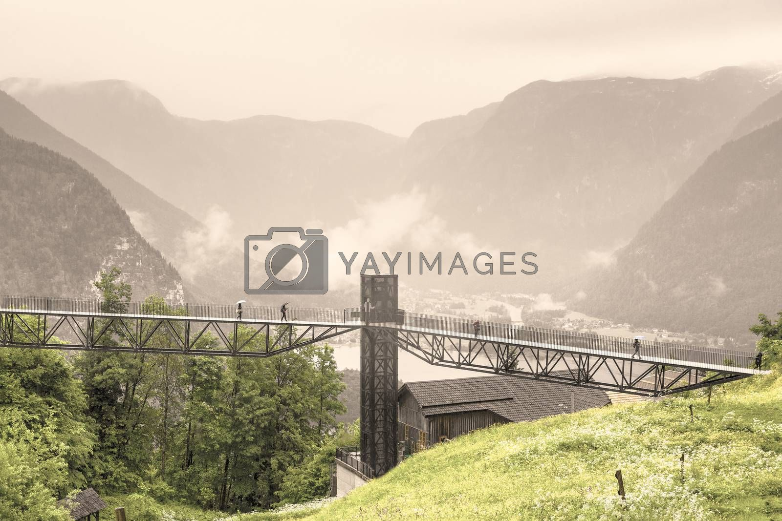 Morning mist, rain and clouds over the Austrian landscape with forests, mountains, pastures, meadows and villages.  View of the lake Hallstattersee in Austria through the pedestrian bridge. Vintage style