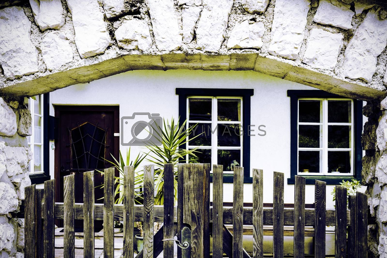 Entrance of the building in Austria, decorated with plants and wooden fence. Traditional Austrian House in Hallstatt in a rainy day. Vintage style