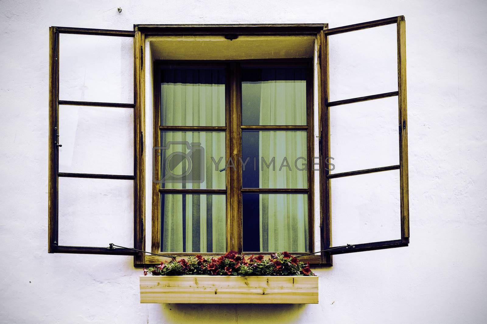Typical window of a house in a small town in Austria. Home in the Austrian city of Hallstatt on a rainy day. Vintage style