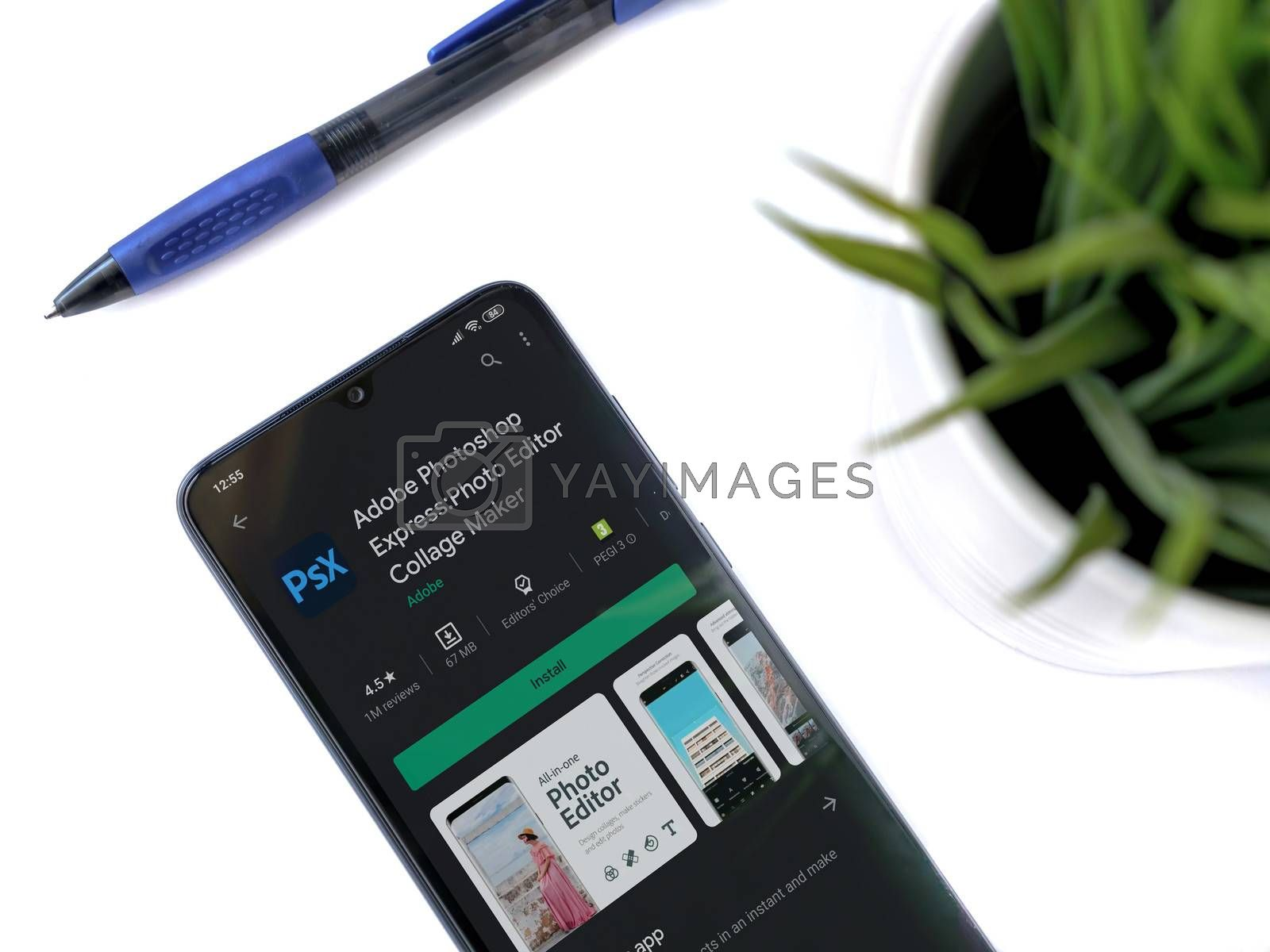 Lod, Israel - July 8, 2020: Modern minimalist office workspace with black mobile smartphone with Adobe Photoshop Express app play store page on a white background. Close up top view flat lay.
