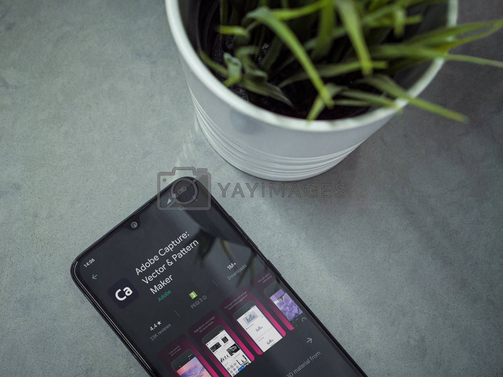 Lod, Israel - July 8, 2020: Modern minimalist office workspace with black mobile smartphone with Adobe Capture app play store page on a marble background. Close up top view flat lay.
