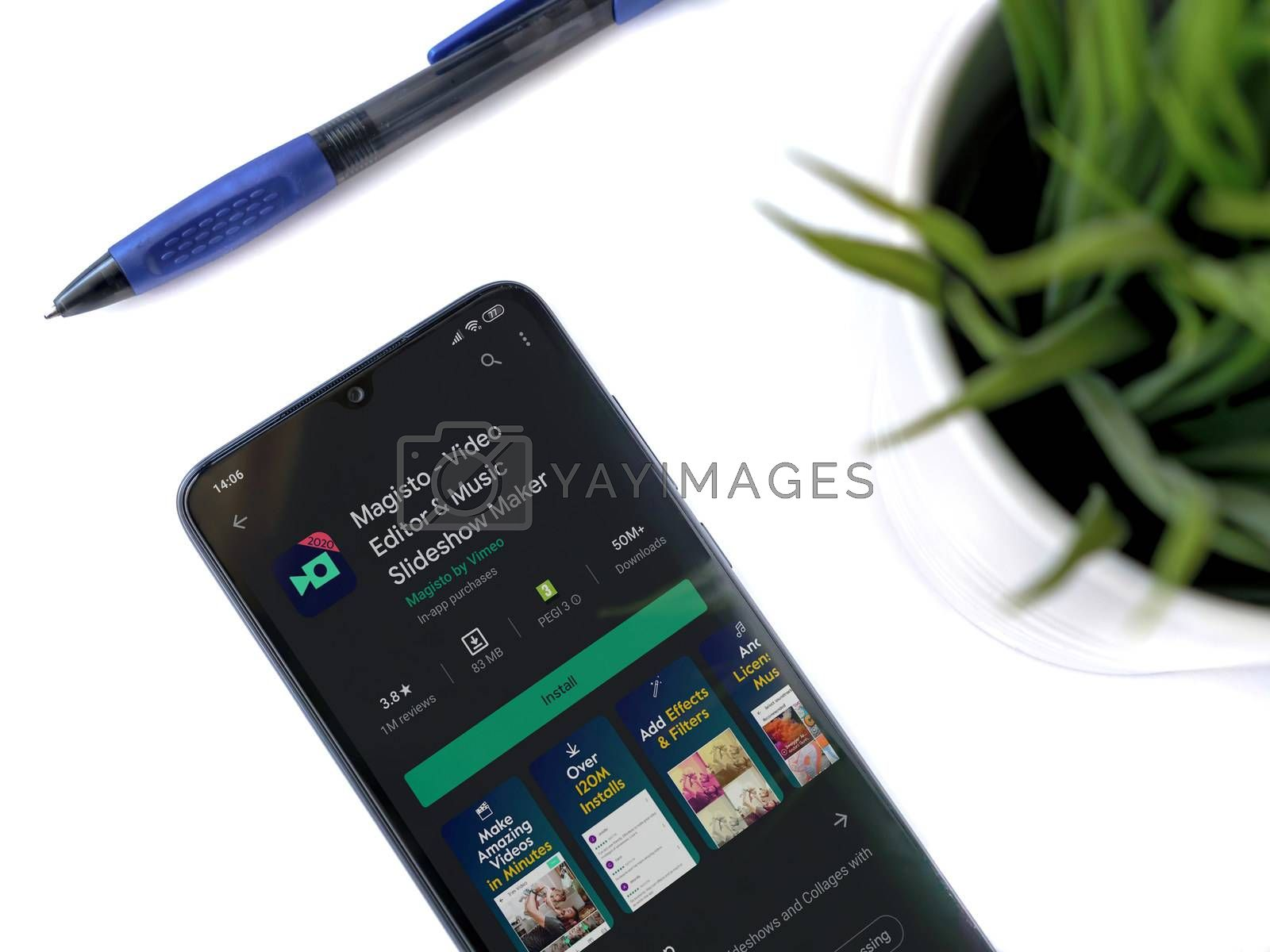 Lod, Israel - July 8, 2020: Modern minimalist office workspace with black mobile smartphone with Magisto - Video Editor & Movie Maker app play store page on white background.Closeup top view flat lay
