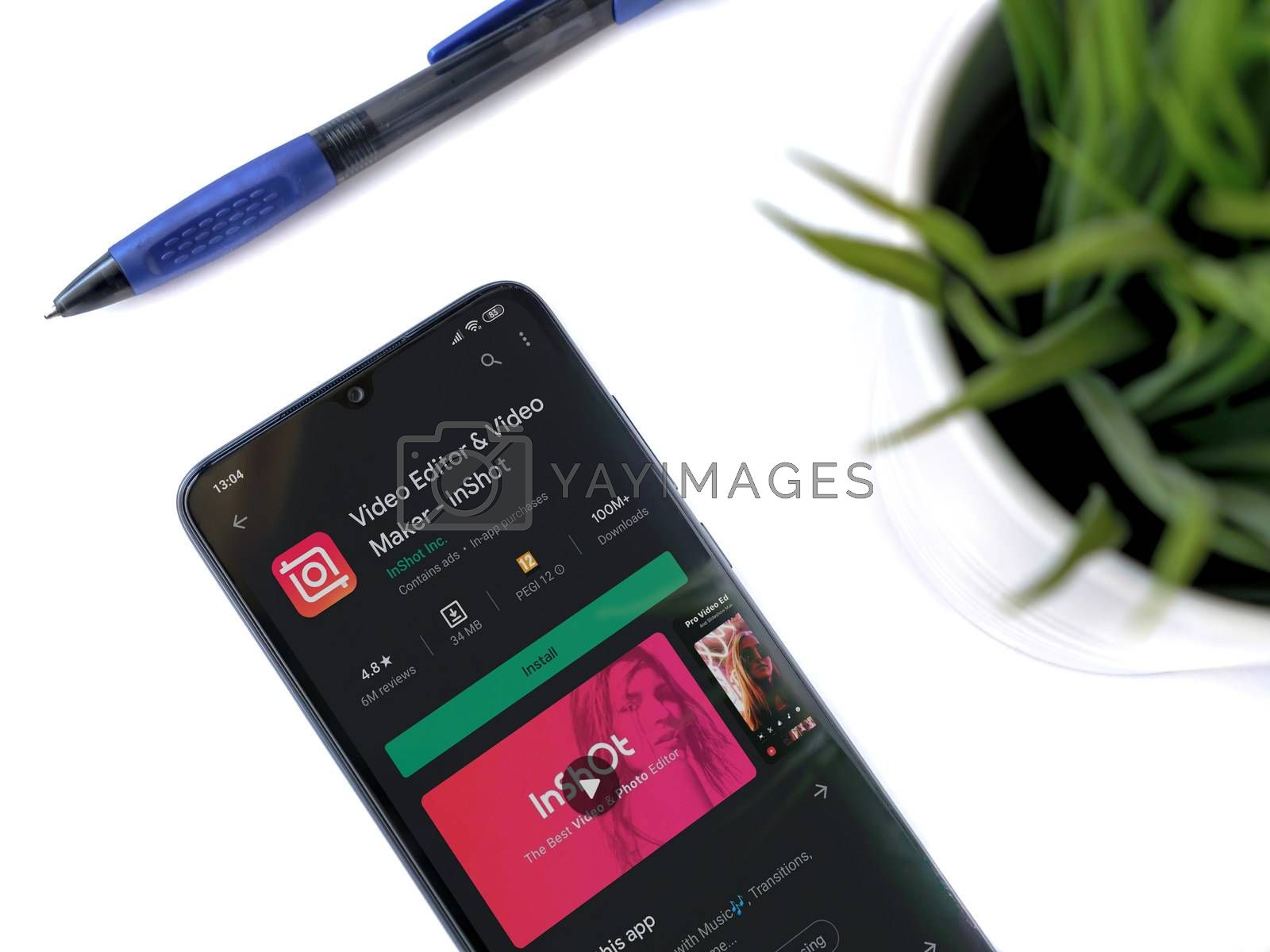 Lod, Israel - July 8, 2020: Modern minimalist office workspace with black mobile smartphone with InShot - Video Editor & Movie Maker app play store page on a white background.Closeup top view flat lay