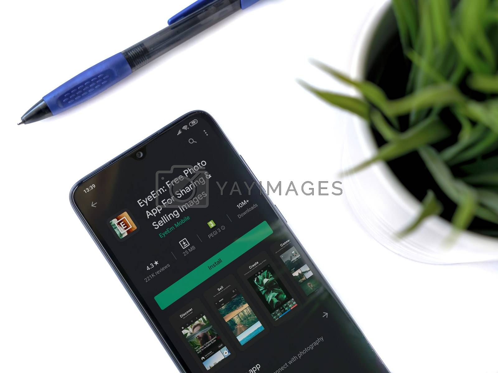 Lod, Israel - July 8, 2020: Modern minimalist office workspace with black mobile smartphone with EyeEm app play store page on a white background. Close up top view flat lay.