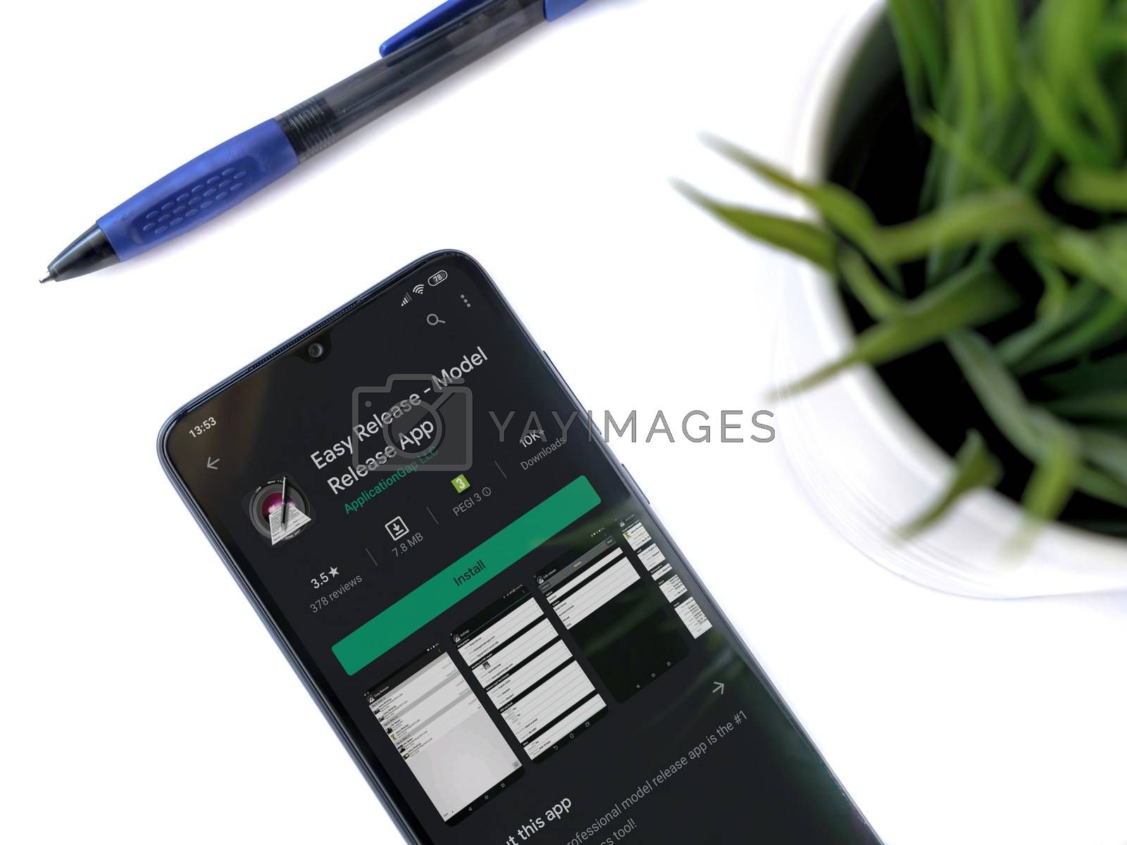 Lod, Israel - July 8, 2020: Modern minimalist office workspace with black mobile smartphone with Easy Release Pro - Model Release app play store page on a white background. Close up top view flat lay