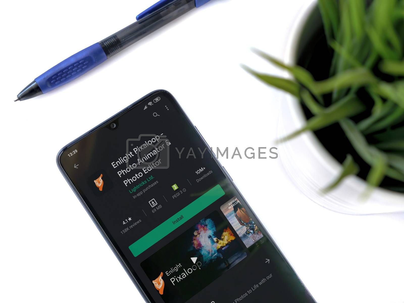 Lod, Israel - July 8, 2020: Modern minimalist office workspace with black mobile smartphone with Enlight Pixaloop app play store page on a white background. Close up top view flat lay.