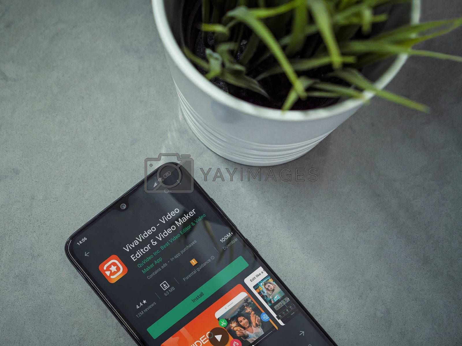Lod, Israel - July 8, 2020: Modern minimalist office workspace with black mobile smartphone with VivaVideo Video Editor & Movie Maker app play store page on marble background.Closeup top view flat lay