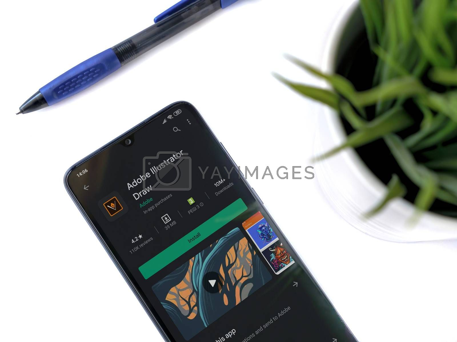 Lod, Israel - July 8, 2020: Modern minimalist office workspace with black mobile smartphone with Adobe Illustrator Draw app play store page on a white background. Close up top view flat lay.