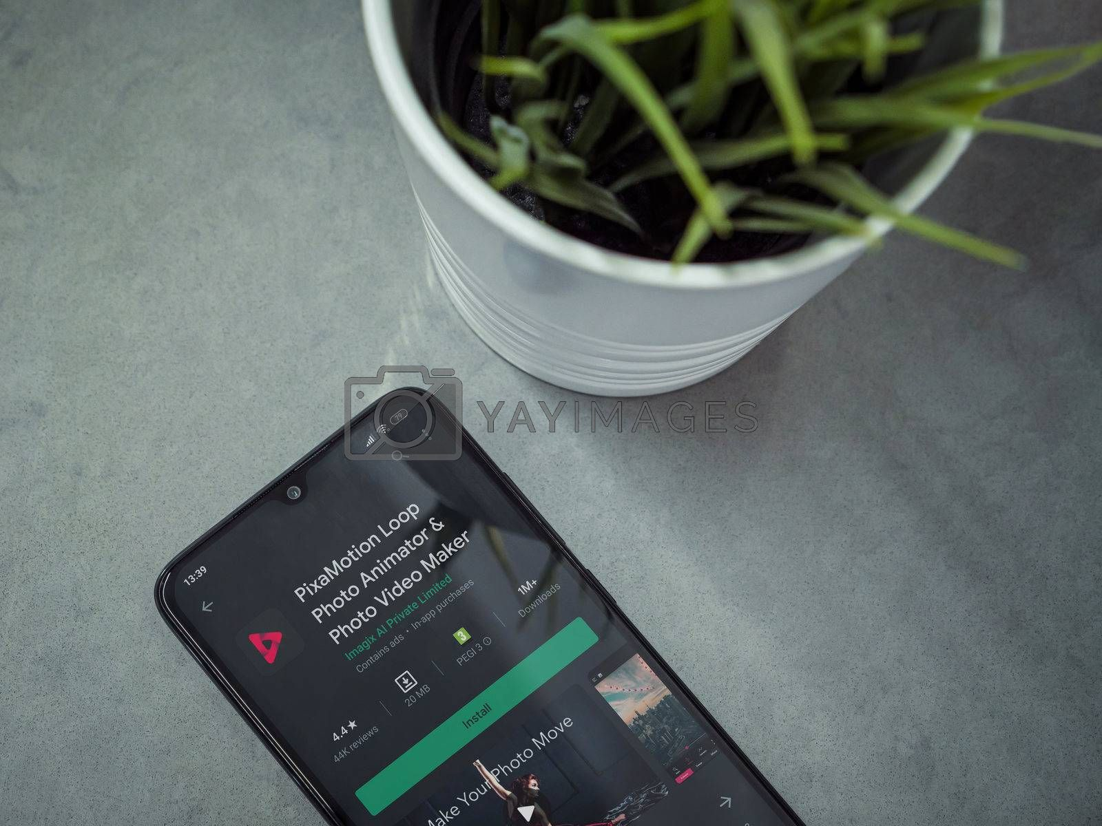 Lod, Israel - July 8, 2020: Modern minimalist office workspace with black mobile smartphone with PixaMotion app play store page on a marble background. Close up top view flat lay.