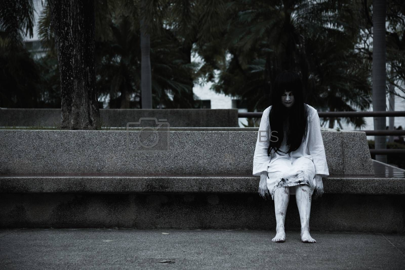 Horror woman ghost creepy sitting under the tree on garden, halloween day concept