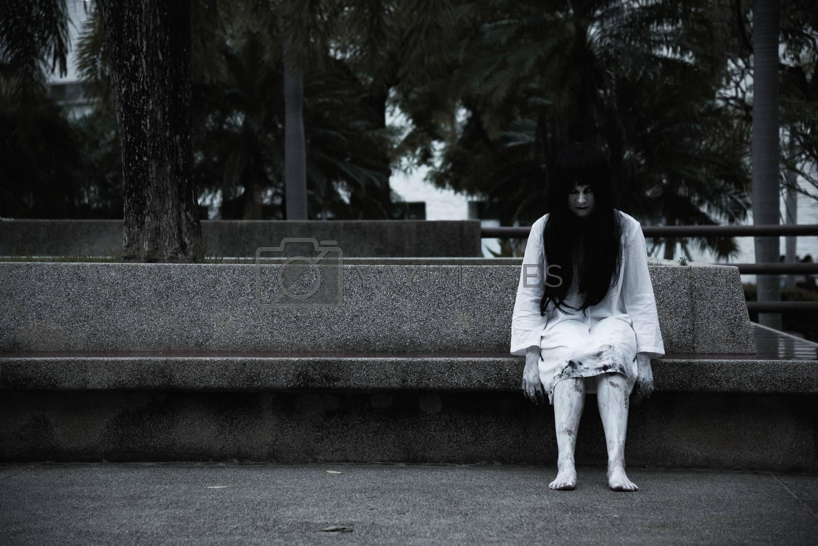 Horror woman ghost creepy sitting under the tree on garden, by Sorapop