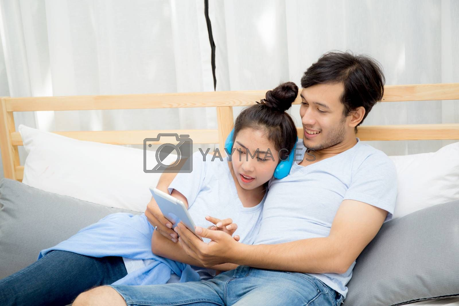 Beautiful asian young couple listening to music with tablet on bed, Love, dating,Young couple in sitting together in bed using a Tablet.