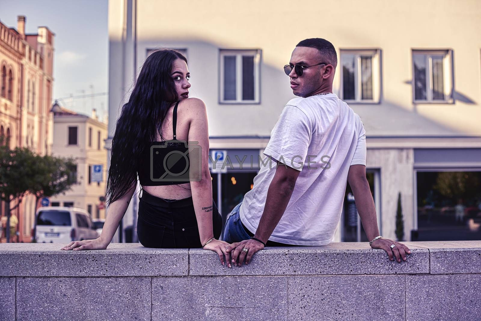 Young Love Couple sitting on a low wall in the city
