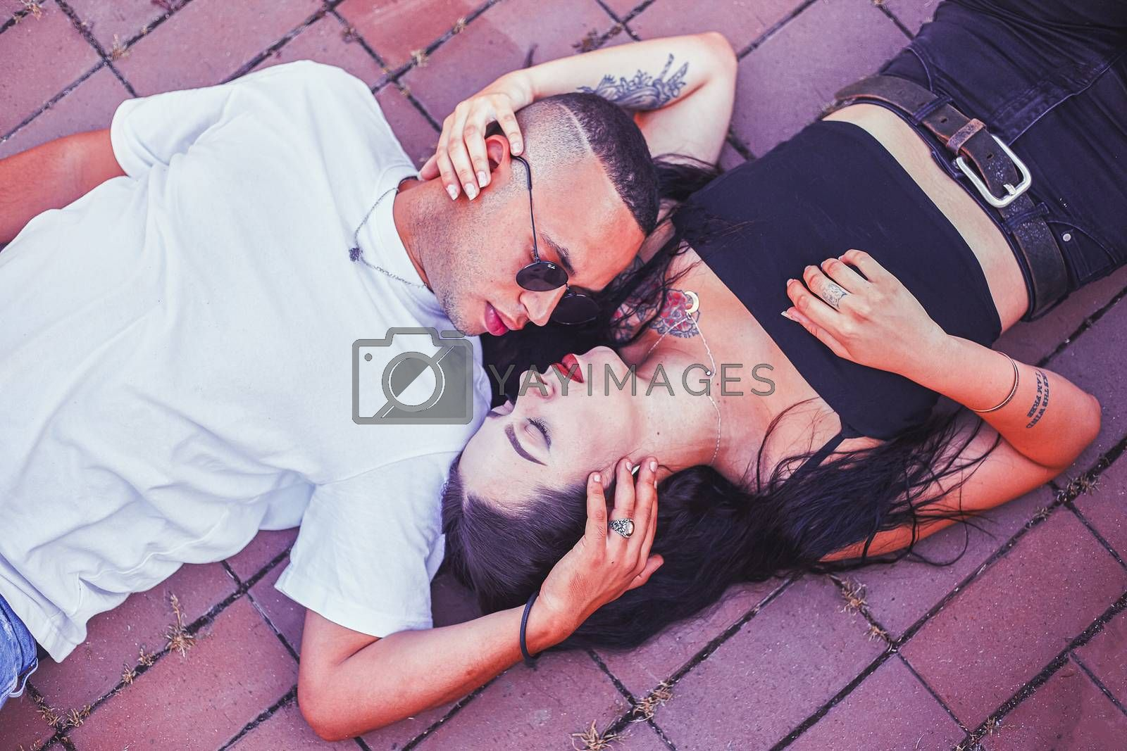 Young Love Couple lying on the ground in the city