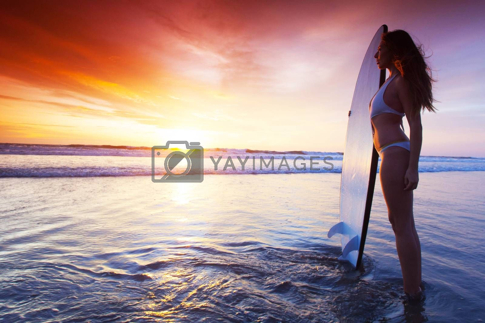 Silhouette of woman on tropical beach holding surfboard at sunset in Bali