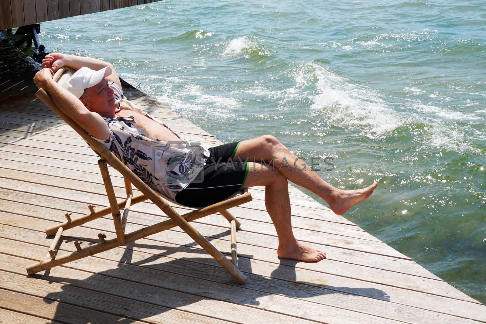 smiling man resting on a sun lounger on the patio near the sea