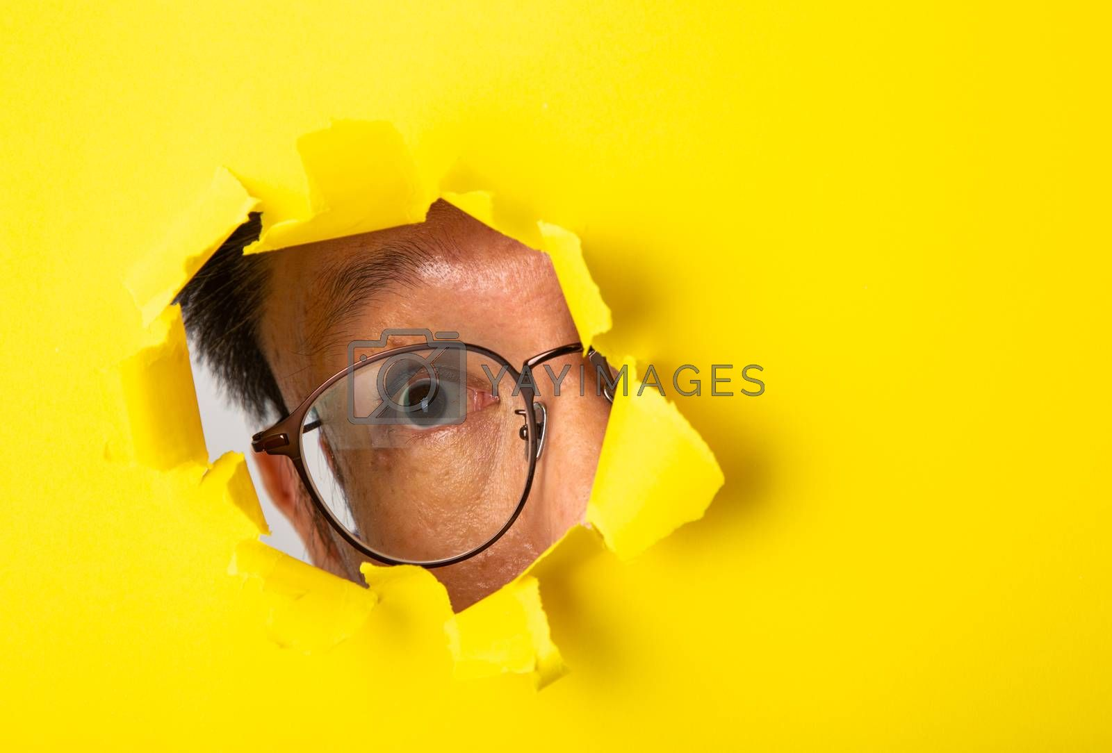 The man with spectacle peeks through a cut hole in the yellow paper background.