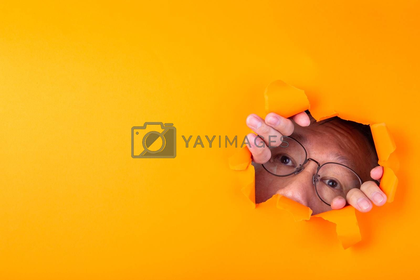 The man with spectacle peeks through a cut hole in the orange paper background.