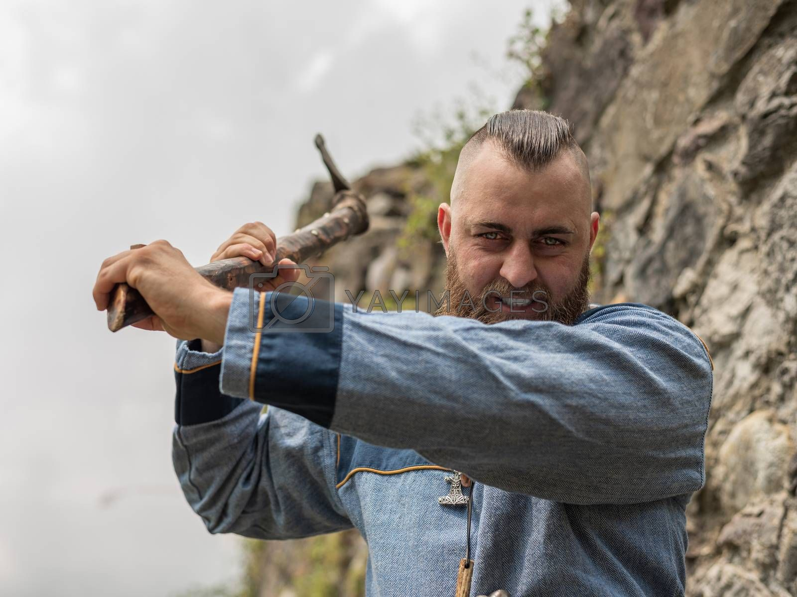 A man in medieval clothes wields an ax in the ruins of an ancient castle, a Viking historical reenactment